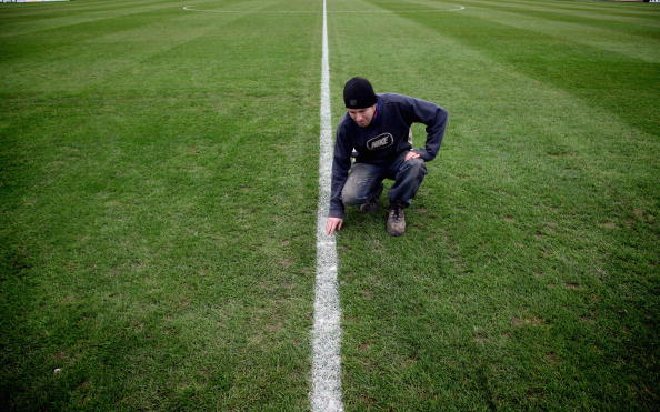 PAULTON, ENGLAND - NOVEMBER 06:  Groundsman Chris Filer examines the freshly painted lines on the pitch at Paulton Rovers Football Club on November 6, 2009 in Paulton, England.  Non-league Paulton Rovers are currently preparing for the single biggest day in their 128-year history as they face Norwich City in the FA Cup first round tomorrow. The Somerset village club - which beat Chippenham Town before being drawn against the League One club - normally has an attendance of 200, but will see capacity at the ground swell to 2500 and the match broadcasted live on television to an estimated audience of 2 million.  (Photo by Matt Cardy/Getty Images)