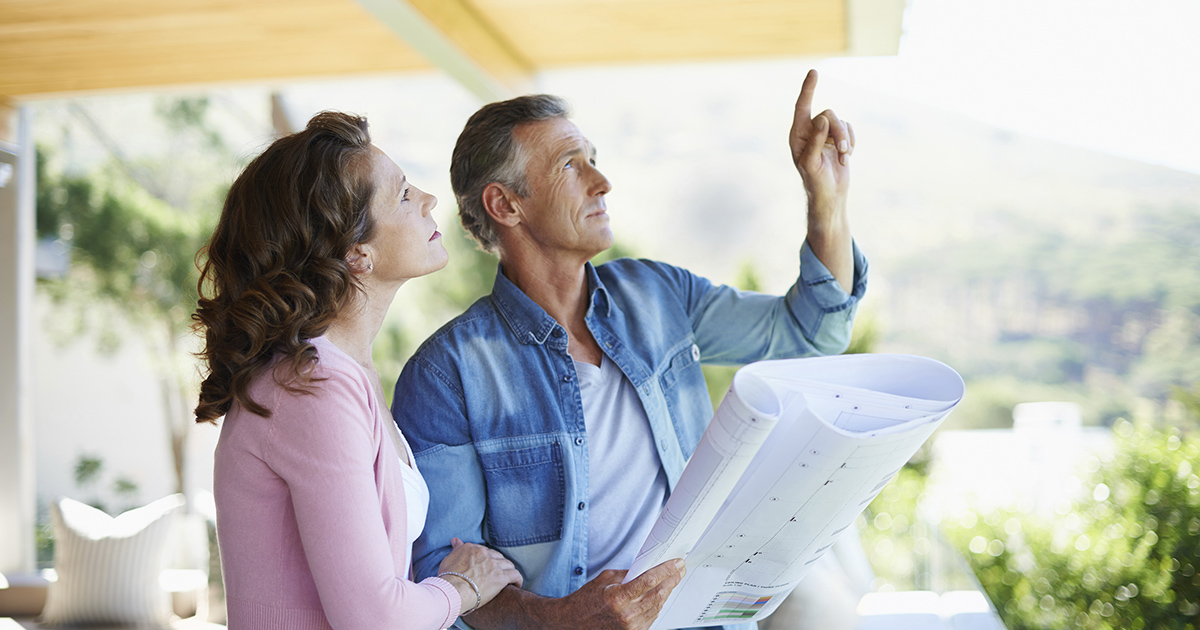 A mature couple looking at architectural plans together at home